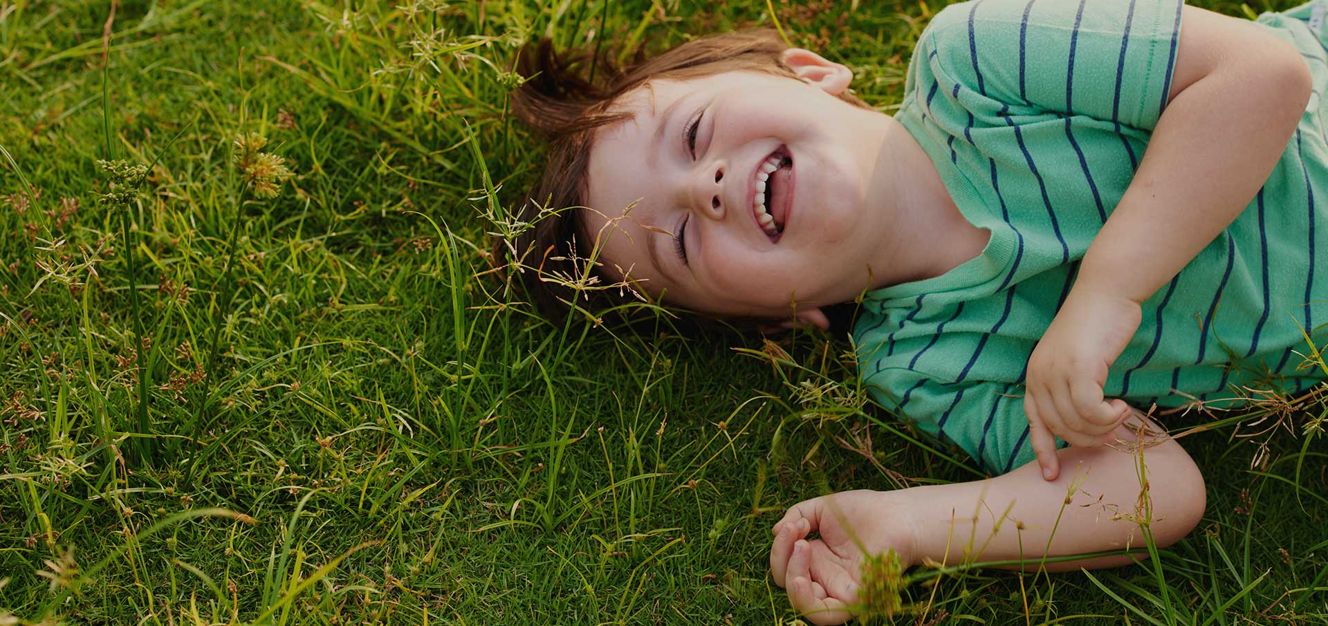 Jonathan Sierk Children's Dentistry | Happy child lying in grass.